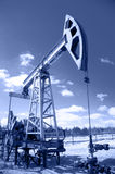 Pump jack and wellhead. Royalty Free Stock Photo