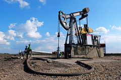 Pump jack and wellheads, Extraction of oil Royalty Free Stock Photos