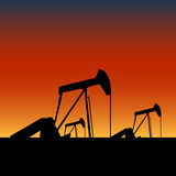 Pump jacks on oil wells at sunset. Vector pump jack dwelling crane extracting crude oil from a well as silhouette, in a sunset view of texas Stock Image