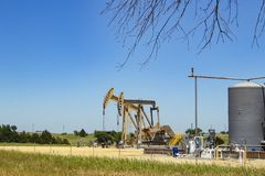 Two pump jacks at a pumping station with tanks and machinery with some farm buildings on the horizon under a blue sky with a few t. 2 pump jacks at a pumping Stock Photo
