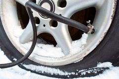 The pump pumps air into the tire in winter. Punched wheel cars. the pump pumps air into the tire in winter stock photo