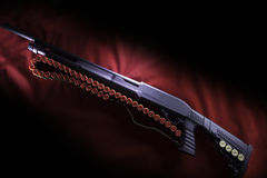 Pump shotgun and bandolier with red shot 12 gauge cartridges on red canvas. Uneven lighting. Black background Stock Photos