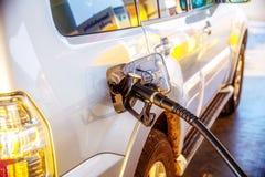 Pumpa bensin tanka i en bil på en bensinstation blåa stängda öde dörrgodor lyfter den målade arbetaren Arkivbilder