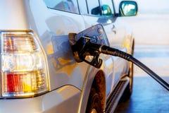 Pumpa bensin tanka i en bil på en bensinstation blåa stängda öde dörrgodor lyfter den målade arbetaren Royaltyfria Foton