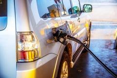 Pumpa bensin tanka i en bil på en bensinstation blåa stängda öde dörrgodor lyfter den målade arbetaren Arkivbild