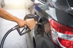 Pumpa bensinbränsle i bil på bensinstationpumpen som tankar Foss royaltyfria foton