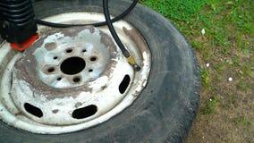 Pumpa det gamla bilhjulet med en kompressor arkivfilmer