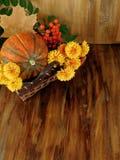 Pumpa i en vide- korg med blommor, rönn och torkar sidor Arkivfoto