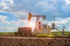 Pumpa stationen för fossila bränslenproduktion med släpet för olje- arbetare royaltyfri foto