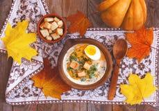Pumpakräm-soppa som dekoreras med lönnlöv, det kokta ägget och c royaltyfria foton