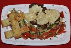 Pumpakrämsoppa med krutonger - en vegetarisk maträtt Soppa i en vit platta på en röd bakgrund royaltyfria bilder