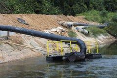 Pumpar och stort rörhandtagvatten från kanalen Arkivfoto
