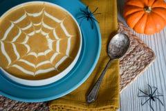Pumpasoppa med Spiderweb gräddfiltoppning Arkivbild