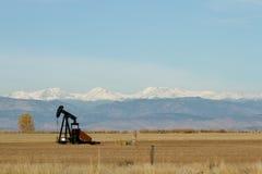 Pumpe Jack auf einem Colorado-Gebiet mit Bergen im Hintergrund lizenzfreies stockfoto
