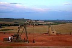 Pumpe Jack mit Feldern und Aufflackern im Hintergrund Stockfotografie