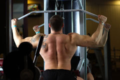 Pumped man pulling weight in gym. Big pumped power-lifter with a tattoo on his arm excersizing in gym Stock Images