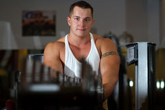 Pumped young man with tattoo in gym. Young pumped power-lifter with a tattoo on his bicep posing in the gym Royalty Free Stock Image