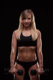 Pumpende Muskeln der schönen athletischen Frau mit den Dummköpfen, lokalisiert auf dunklem Hintergrund mit copyspace Stockfotografie