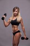 Pumpende Muskeln der schönen athletischen Frau mit den Dummköpfen, lokalisiert auf grauem Hintergrund mit copyspace Stockfotografie