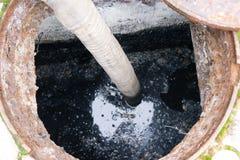 Pumpendes Abwasser des Mannes vom Loch Stockfotos