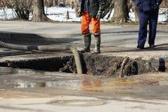 Pumpendes Wasser aus der Grube heraus, wenn ein Unfall beseitigt wird: Brechen von Rohren mit kaltem Wasser Stockfoto