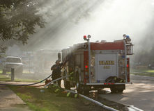 Pumper Truck. A fire truck used to pump water. They are putting out a small house fire Royalty Free Stock Photography