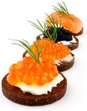Pumpernickel bread with salmon, trout and sturgeon caviar Stock Photos