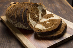 Pumpernickel and rye swirl bread Slices on cutting board. Abstract Pumpernickel and rye swirl bread on cutting board on wood background Stock Images