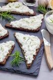 Pumpernickelbröd med feta, gräddost, rosmarin, citron, vitlökdopp Arkivfoto