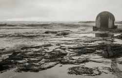 Pumphouse located on rocks as the waves roll in. Black and white image of pumphouse located on rocks as the waves roll in on a couldy morning Stock Photos