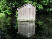 Pumphouse on the Pond. In Countryside Park, Avon, CT.  Mirror image of pumphouse reflected on the pond Stock Photo