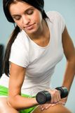 Pumping biceps. Close-up of young woman sitting with barbell in hand and lifting it Stock Photo