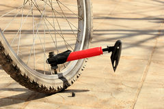 Pumping bicycle wheel red bicycle pump. Royalty Free Stock Photography