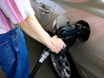 Pumping Gas. Shows the safe and proper way to hold the nozzle and pump gasoline into a car at a self serve gas station royalty free stock photos