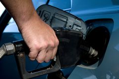 Pumping Gas. Close up of man hand holding gas pump handle and filling the fuel tank on his vehicle Stock Photo