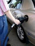 Pumping Gas (3). Shows the safe and proper way to hold the nozzle and pump gasoline into a car at a self serve gas station royalty free stock images
