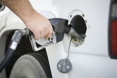 Pumping Gas. Man's hand holding gas pump while fueling Stock Image