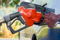 Pumping gas in car on station. Red gas pump nozzle in action Royalty Free Stock Photos