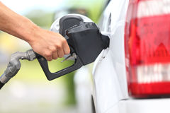 Pumping gas at gas pump. Closeup of man pumping gasoline fuel in car at gas station royalty free stock photo