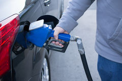 Pumping gas at gas pump. Closeup of man pumping gasoline fuel in. Car at gas station Royalty Free Stock Images