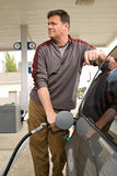 Pumping Gas at the Gas Station. Handsome man filling up his gas tank for his car at the gas station Stock Photos