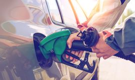 Pumping gas. Hand holding fuel nozzle. Pumping gas at gas station. Hand holding fuel nozzle. Gasoline economy concept stock image