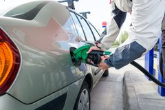 Pumping gas. Hand holding fuel nozzle. Stock Photo