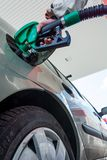 Pumping gas. Hand holding fuel nozzle. Stock Photos