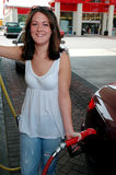 Pumping Gas - Happy. Smiling young woman pumping gas Royalty Free Stock Photos