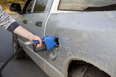 Pumping gas into a pickup truck. Man pumping gas into a pickup truck Royalty Free Stock Images