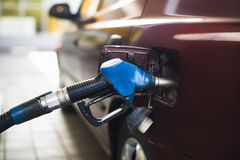 Pumping gasoline fuel in car at gas station. Transportation and ownership concept - man pumping gasoline fuel in car at gas station stock images
