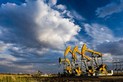 Pumping unit. An industrial oil pump under a hot sky royalty free stock image