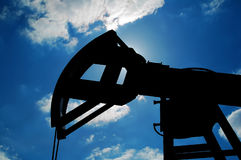 Pumping unit. Machine-rocking chair on blue sky background Stock Photo