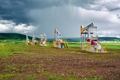 Pumping unit for pumping oil on a background of cumulus clouds and rainfall Stock Photos